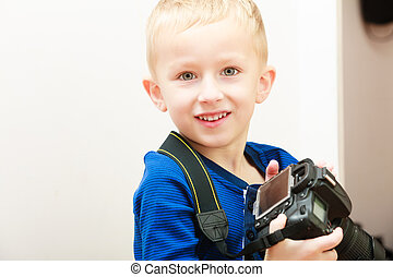 Portrait of happy boy child kid playing with camera. At home.