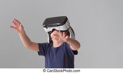 Portrait of happy boy in a virtual reality headset. Attractive kid using vr goggles at home. Entertainment technology, futuristic gadgets and generation Z concept.