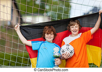 Portrait of happy boys with trophy and soccer ball holding German flag against net