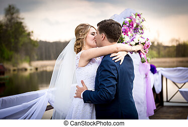 happy bride and groom kissing on sunset at river