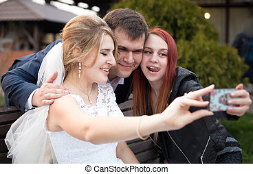happy bride and groom making selfie with guest on wedding...