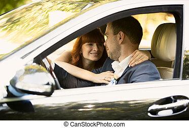 happy bride and groom riding a car
