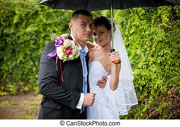 Portrait of happy bride and groom standing under umbrella