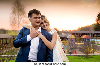 happy bride hugging groom from back at beautiful sunset