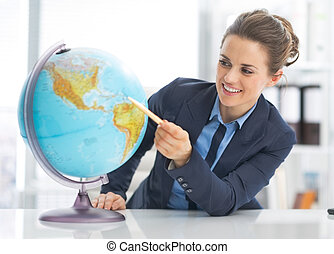 Portrait of happy business woman pointing on earth globe