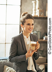Portrait of happy business woman with coffee latte in loft apart
