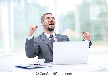 Portrait of happy businessman cheering at workplace -...