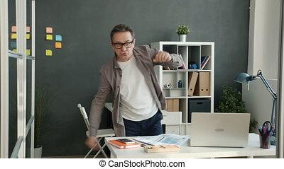 Portrait of happy businessman dancing having fun in office looking at camera
