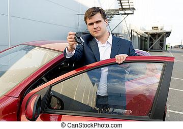 Portrait of happy businessman posing at car with keys