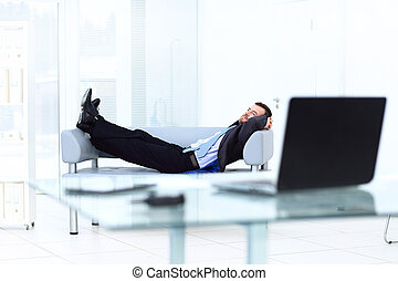 Portrait of happy businessman relaxing in office