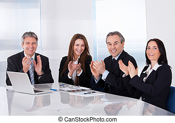 Portrait Of Happy Businesspeople Clapping In Office