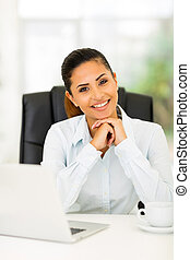 happy businesswoman sitting in office
