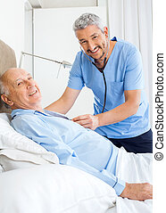 Portrait Of Happy Caretaker Examining Senior Man