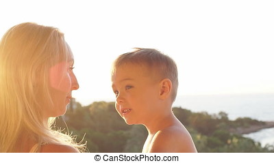 Portrait of happy caucasian family at sunset. Laughing mother and son in sunset. Slow Motion