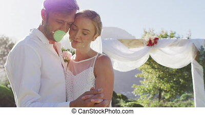 Portrait of happy caucasian newly wed couple, dancing in front of altar outdoors. romantic summer wedding outdoors.