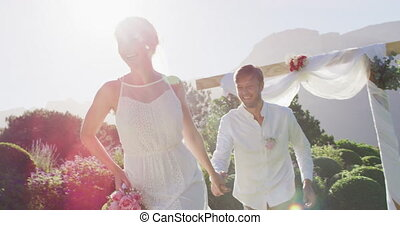 Portrait of happy caucasian newly wed couple running from altar outdoors. romantic summer wedding outdoors.