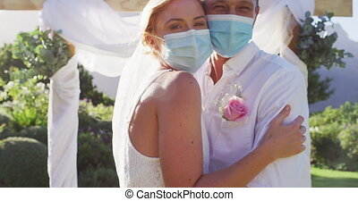 Portrait of happy caucasian newly wed couple touching heads at altar, wearing face masks. romantic summer wedding coronavirus covid 19 pandemic.
