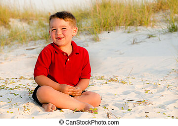Portrait of happy child on beach with sand dunes in background