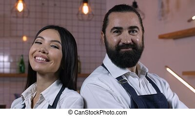 Portrait of happy coffee shop owners smiling - Portrait of...