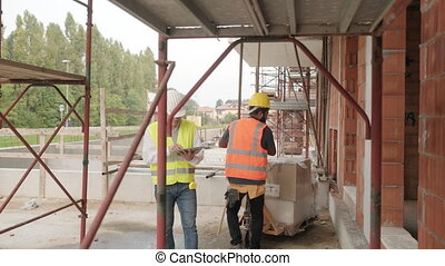 Portrait Of Happy Construction Site Supervisor Talking To Manual Worker