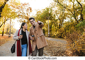 Portrait of happy couple drinking takeaway coffee from paper cups while walking in autumn park