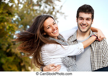 Portrait of happy couple embracing outdoors.