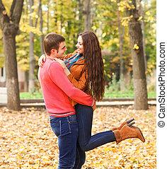 Portrait of happy couple enjoying golden autumn