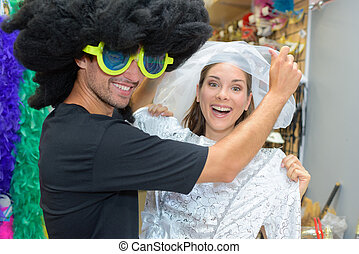 portrait of happy couple having fun trying costumes