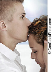 Portrait of happy couple in love, boyfriend kissing girlfriend on forehead
