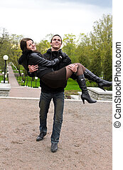 Portrait of happy couple in park. Holding the girl in his arms.