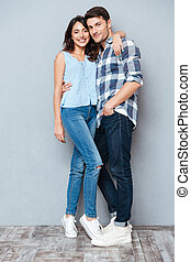 Portrait of happy couple looking at camera over gray background