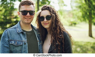 Portrait of happy couple man and woman wearing sunglasses and trendy clothing looking at camera and smiling with beautiful green park in background.