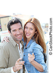 Portrait of happy couple pointing at camera