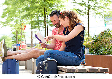 Portrait of happy couple sitting and reading together outside on bench