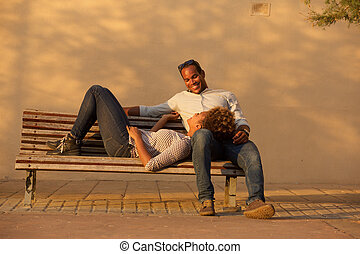 happy couple sitting on park bench outside