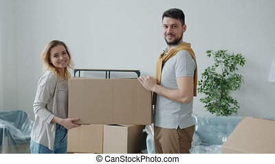Portrait of happy young couple smiling looking at camera holding carton box during relocation to new house. Family lifestyle and housing concept.