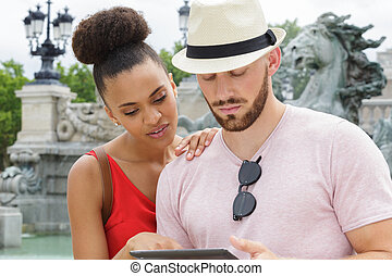 portrait of happy couple using digital tablet in city