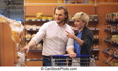 Portrait of happy cute couple choosing fresh breads in supermarket
