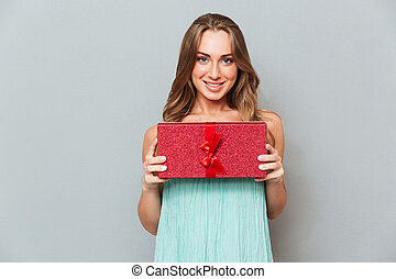 Portrait of happy cute young woman with gift box