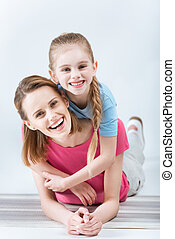 portrait of happy daughter hugging laughing mother on white