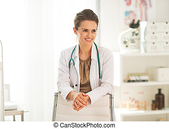 Portrait of happy doctor woman in office
