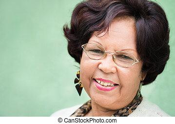 Portrait of happy elderly black lady with eyeglasses smiling...