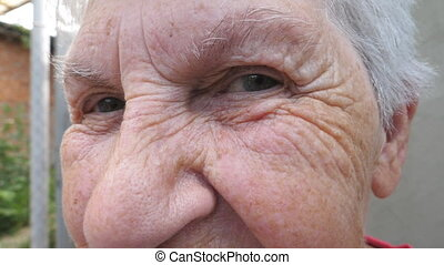 Portrait of happy elderly woman smiling and looking into camera outside. Close up wrinkled face of gray-haired grandmother outdoor. Positive facial expression of old granny. Slow motion