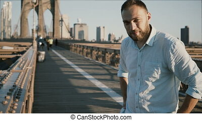 Portrait of happy European freelance worker smiling at camera, leaning to Brooklyn Bridge rails in New York City 4K.