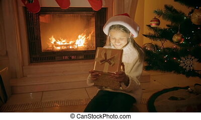 Portrait of happy excited girl sitting at fireplace opens Christmas gift box