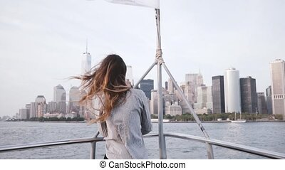 Portrait of happy excited tourist girl with flying hair enjoying New York skyline view from a tour boat slow motion.
