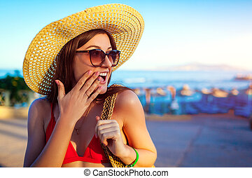 Portrait of happy excited woman in hat walking on beach. Summer vacation