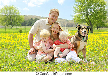 Portrait of Happy Family and Dog in Flower Meadow