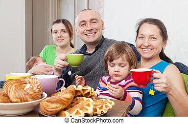 Portrait of happy family having tea