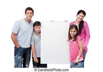 Portrait Of Happy Family Holding Blank Billboard